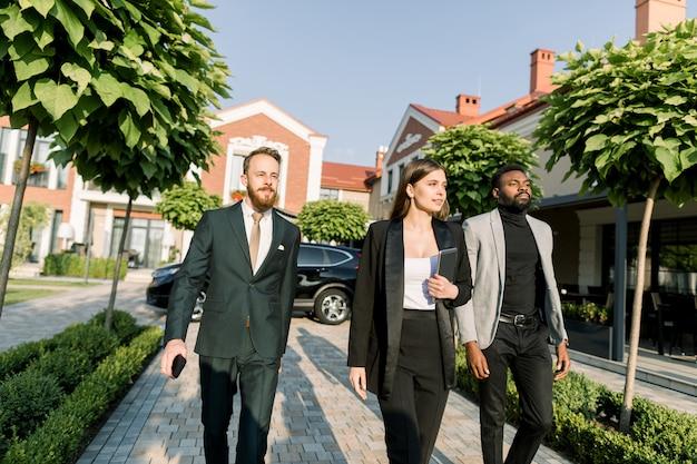Squadra di uomini d'affari multietnici due uomini e donne in abbigliamento casual elegante, camminando all'aperto sulla riunione d'affari. la donna tiene la tavoletta digitale. auto nera ed edifici moderni