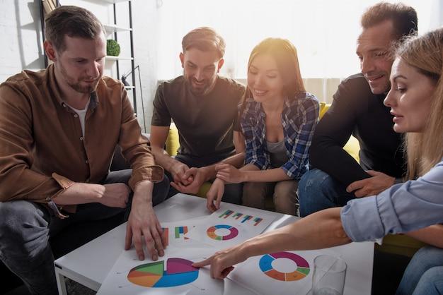 Team di persone lavorano insieme in ufficio con le statistiche dell'azienda. concetto di lavoro di squadra e collaborazione.