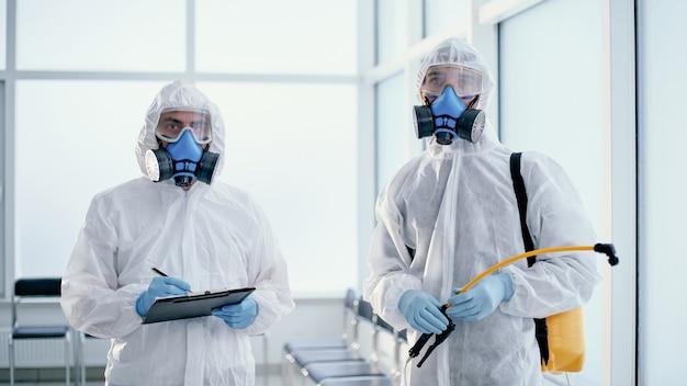 Il team di disinfettanti maschili professionisti lavora in un edificio pubblico. foto con copia-spazio.