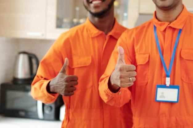 Team di idraulici professionisti che mostrano pollice in su dopo aver terminato il lavoro in casa del cliente