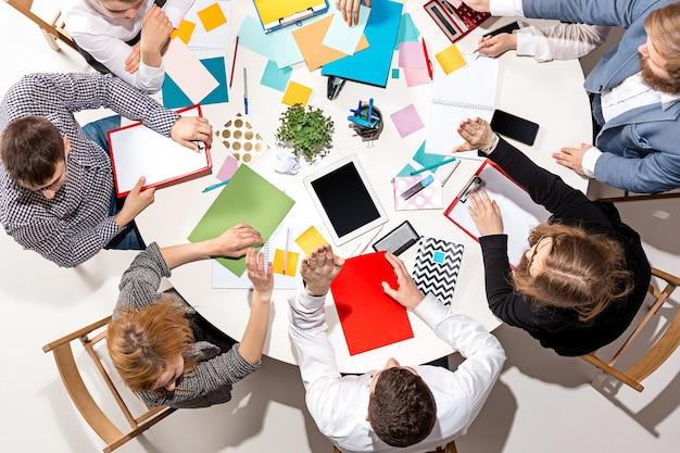 Squadra che si siede dietro la scrivania che controlla i rapporti che parlano vista dall'alto Foto Premium