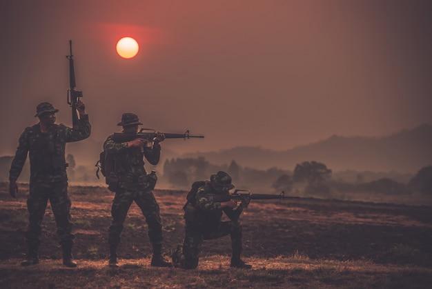 Forze speciali della squadra. fucile d'assalto più vecchio con silenziatore. i soldati di azione di sagoma tengono le armi. concetto militare e di pericolo.