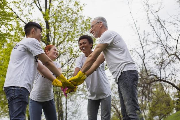 Spirito di squadra. basso angolo di ottimisti volontari vigorosi in piedi e tenendosi per mano insieme