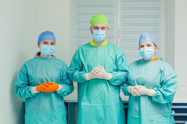 Un team di tre dentisti si prepara per la chirurgia e il trattamento dentale con mascherine e camici medici