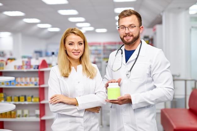 Una squadra di due farmacisti caucasici sta mostrando la scatola della medicina