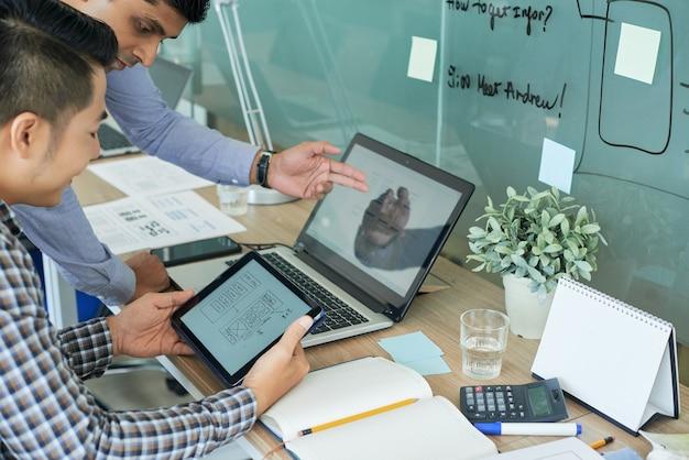 Team di progettisti dell'interfaccia utente che lavorano sull'interfaccia della nuova applicazione mobile e confrontano i layout sullo schermo del tablet e del laptop