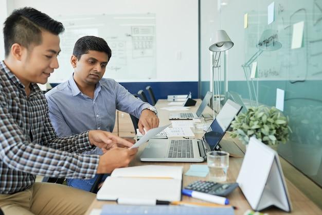 Team di designer ui e ux che discutono del documento con il layout dell'interfaccia del sito web e scelgono cosa aggiungere e cosa cambiare