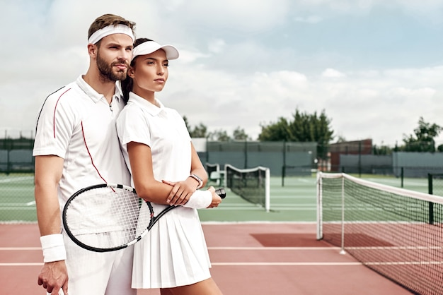 La bella coppia di lavoro di squadra è pronta per giocare a tennis