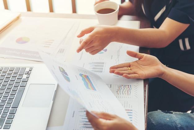 Processo di lavoro di squadra. due donne d'affari con laptop e grafico cartaceo in ufficio open space. concetto di affari.