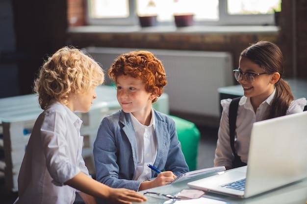 Lavoro di squadra. tre bambini carini che discutono di qualcosa e sembrano eccitati