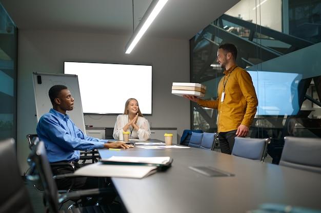 Squadra di lavoratori mangia pizza, pranzo di lavoro in ufficio it. lavoro di squadra professionale e pianificazione, brainstorming di gruppo e lavoro aziendale, interni moderni dell'azienda sullo sfondo