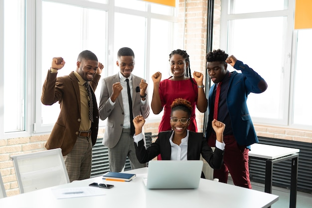 Squadra di giovani africani in ufficio al tavolo con i laptop
