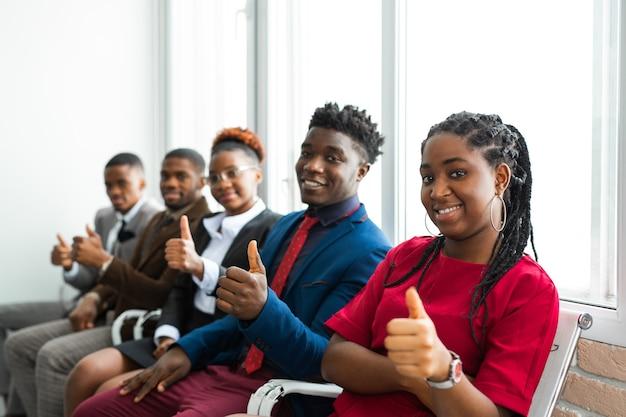 Squadra di giovani africani in ufficio con il gesto della mano