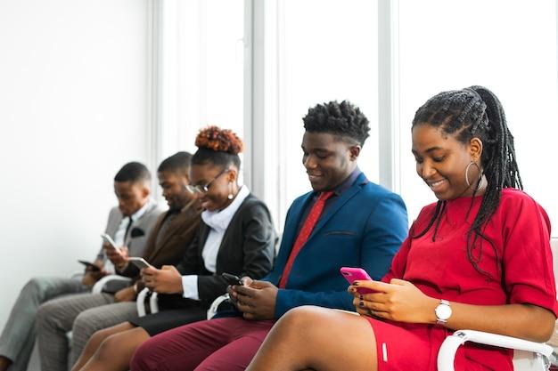 Squadra di giovani africani in ufficio con i telefoni cellulari