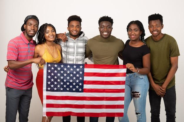 Squadra di giovani belle persone sul muro bianco con la bandiera americana