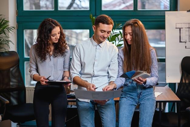 Squadra di giovane ingegnere caucasico in piedi vicino al tavolo mentre parla di nuova idea di piani di costruzione in ufficio moderno elegante.