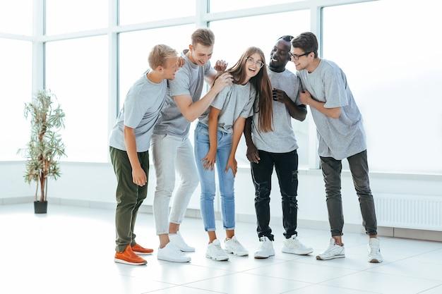 Team di giovani professionisti in piedi in un ufficio luminoso