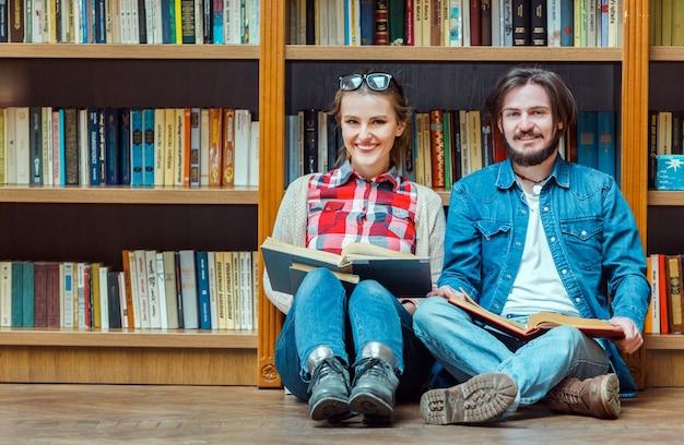 Team di giovani studenti con libri in una biblioteca