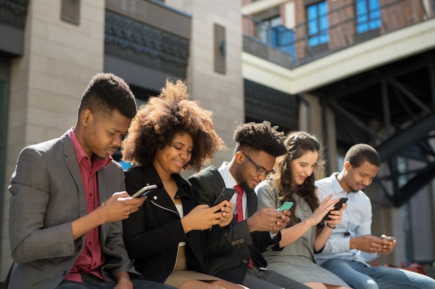 Team di giovani di successo con i telefoni cellulari