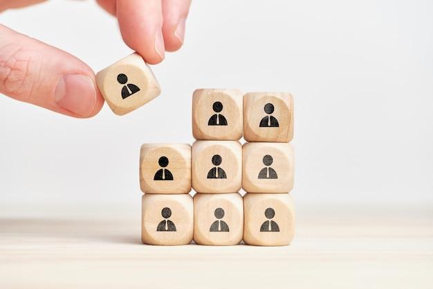 Concetto di teambuilding e lavoro di squadra su cubi di legno con dipendente personas astratto.