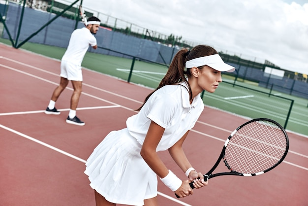 Lavoro di squadra bella donna e bell'uomo stanno giocando a tennis