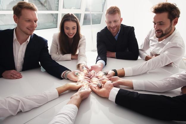 Concetto di lavoro di squadra e brainstorming con uomini d'affari che condividono un'idea con una lampada. avvio di una società di concept