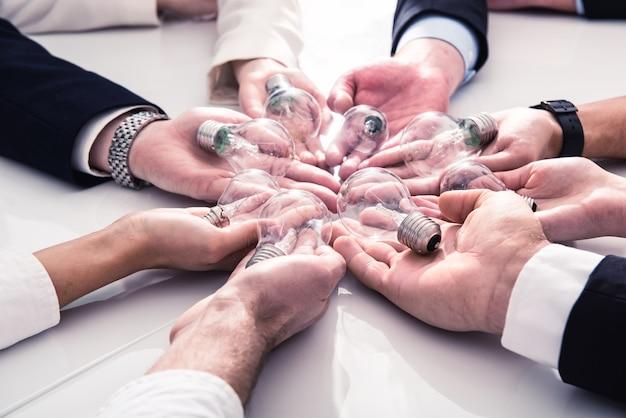 Concetto di lavoro di squadra e brainstorming con uomini d'affari che condividono un'idea con un concetto di lampada di avvio