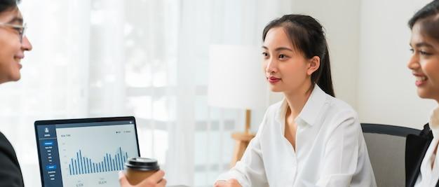 Riunione di brainstorming di lavoro di squadra e nuovo progetto di avvio sul posto di lavoro, imprenditori asiatici sorridenti che lavorano al computer portatile con documenti grafici.