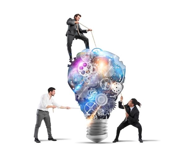 Il lavoro di squadra di uomini d'affari lavora insieme a un sistema di ingranaggi a lampadina