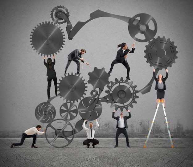 Il lavoro di squadra degli uomini d'affari lavora insieme a un sistema di ingranaggi