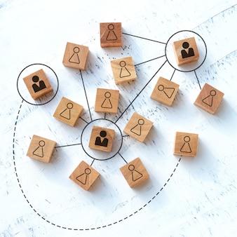 Concetto di lavoro di squadra e comunicazione, blocchi di legno rettangolari su un tavolo di legno bianco.