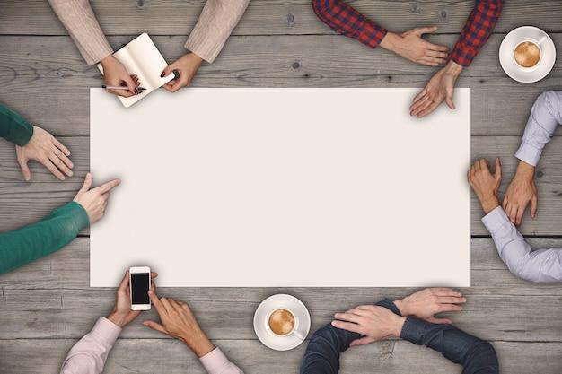 Concetto di lavoro di squadra e cooperazione - vista dall'alto di sei persone che disegnano o scrivono su un grande foglio di carta bianco sulla tavola di legno.
