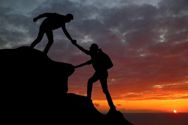 Il lavoro di squadra delle coppie che fa escursioni si aiuta a vicenda a fidarsi della sagoma di assistenza in montagna, al tramonto. lavoro di squadra di un uomo e di una donna che si aiutano a vicenda in cima alla squadra di alpinismo