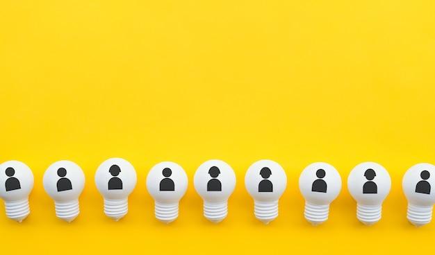 Piatto di lavoro di squadra giaceva con l'icona umana sul gruppo di lampadine in colore pastello