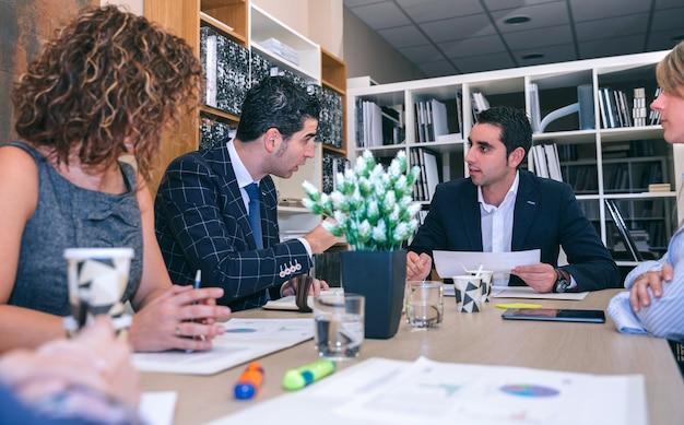 Lavoro di squadra che ha una riunione sulla strategia aziendale seduto al tavolo nella sede dell'azienda