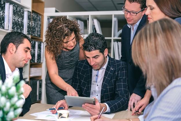 Documento dall'aspetto del lavoro di squadra nella tavoletta elettronica intorno al capo aziendale nella sede centrale dell'azienda