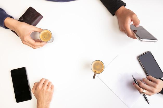 Riunione di lavoro di squadra su un tavolo, con mani e caffè, vista dall'alto