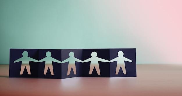 Concetto di lavoro di squadra, partenariato, umanità e unità. forma di segno umano ritagliata su carta piegata