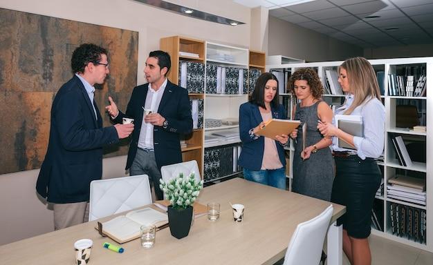 Lavoro di squadra in piedi e parlare dopo un incontro di lavoro nella sede dell'azienda
