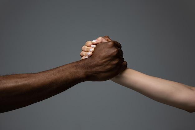 Lavoro di squadra insieme tolleranza razziale rispettare l'unità sociale mani africane e caucasiche