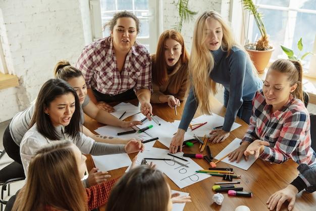 Lavoro di squadra. giovani che discutono sui diritti delle donne e sull'uguaglianza in ufficio. donne d'affari o impiegati caucasici si incontrano per problemi sul posto di lavoro, pressioni maschili e molestie.
