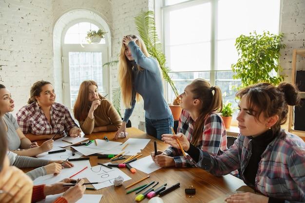 Lavoro di squadra giovani che discutono di diritti e uguaglianza delle donne in ufficio