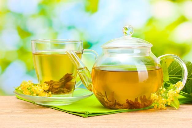 Teiera e tazza con tè di tiglio e fiori sulla tavola di legno in giardino