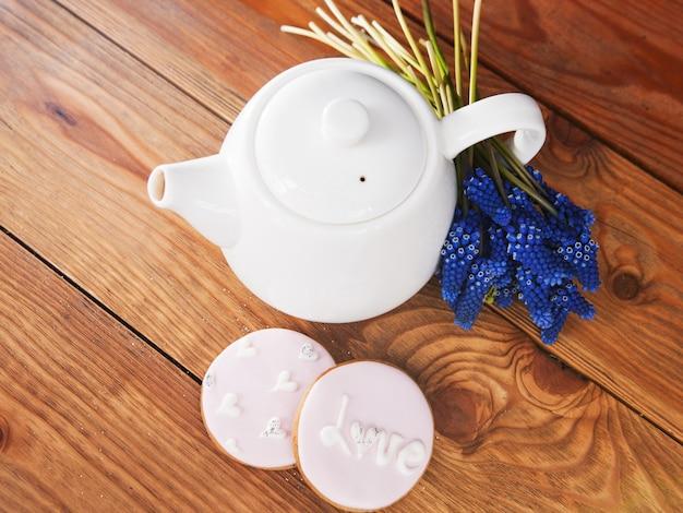 Teiera e panpepato con vista dall'alto muscari. bella mattina, colazione, celebrazione del tea party, tavolo in legno, concetto di sfondo