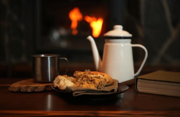 Teiera e tazze sulla tavola di legno dell'annata.