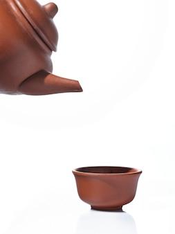 Teiera e tazza da tè su sfondo isolato