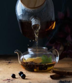 Una teiera con tè nero con bacche di ribes limone un bastoncino di cannella sfondo autunnale spazio copia
