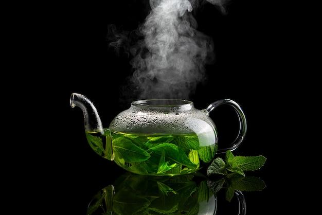 Teiera con infuso di tè alla menta su uno sfondo nero con vapore in aumento sopra di esso