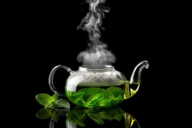 Teiera con tè alla menta preparato su uno sfondo nero con vapore in aumento sopra di esso