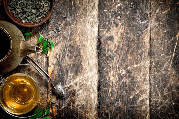 Teiera con fragrante tè indiano. su uno sfondo di legno.
